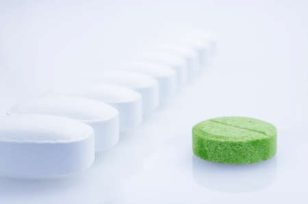 white pills: Close-up. Green pill on a light background, and white pills Stock Photo