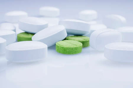 white pills: Close-up. Green pills on a light background, and white pills Stock Photo