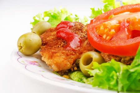 pork chop: Pork chop with salad and olives on a light background