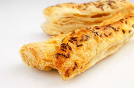 Confectionery theme. Puff pastry, topped with caraway seeds, on white surface. Stock Photo