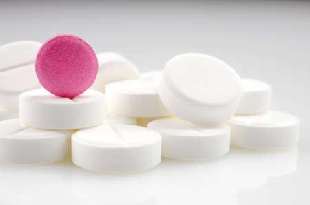 white pills: Close-up. Pink pill standing on a heap of white pills.