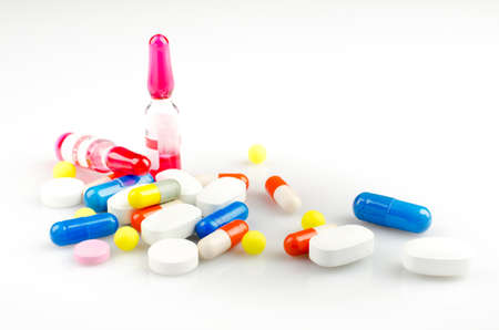 Pharmacy theme. Multicolored Isolated Pills, Ampules and Capsules on the White Surface. Closeup