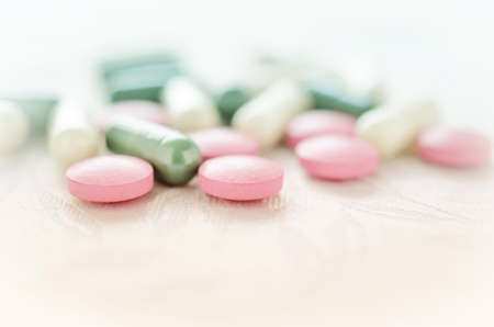 Pink, white and green pills tablets medicine on white background isolated