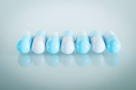 Pharmacy theme. A row of Blue and White Isolated Capsules on the White Surface. Closeup.