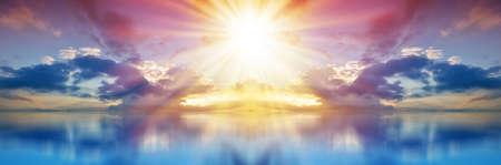 色の夕日。パノラマ空の雲と青い海を越え、太陽