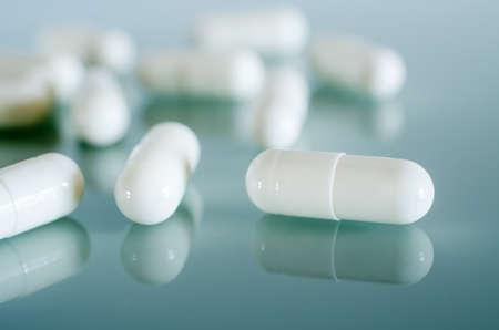 Pharmacy theme. White medical capsules lie on the blue mirror surface. Closeup Banco de Imagens
