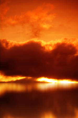 Red sunset over sea, rich dark clouds, Bright sun rays