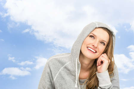 Adult woman in a sport coat with a hood against the winter sky  Smiling  Closeup  Stock Photo