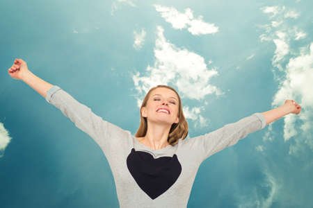 Woman with heart raising arms above her head and the sky as a background photo
