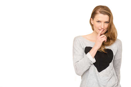 A woman whispering and watching suspiciously with her finger on her mouth
