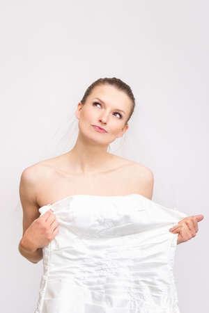 resolving: Giovane sposa-to-be provare sul suo abito - controllando il vestito