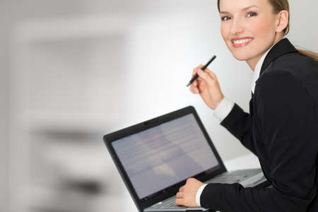 Business woman showing laptop screen and pen