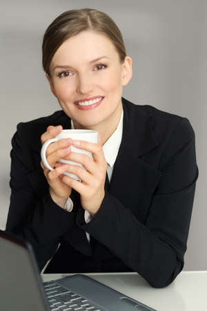 Happy woman sitting in armchair with laptop computer, holding coffee mug, looking at camera