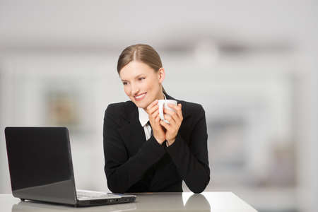 Smiling businesswoman sitting with laptop computer, holding coffee and tea mug photo