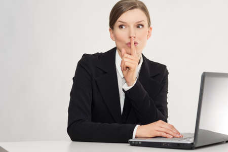 Woman with laptop whispering, with secret in the office Stock Photo