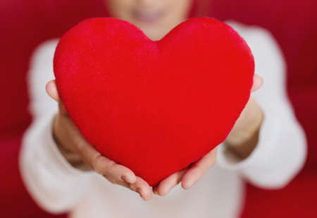 Beautiful woman holding heart in hand - care and love