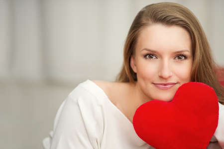 Woman in love with heart in hand - portrait for Valentines Day Stock Photo