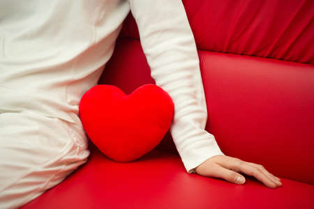 Lonely heart on sofa - Valentine and loneliness Stock Photo