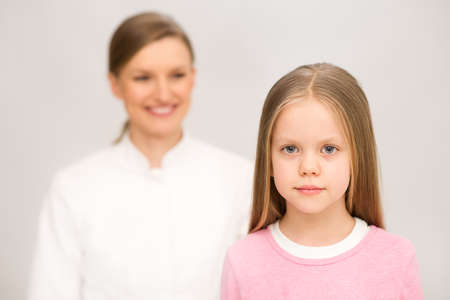 Mother and nurse examining little daughter  Isolated on white background
