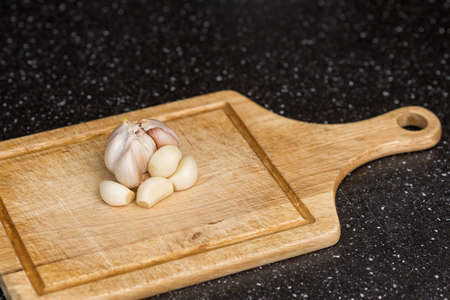 Delicious fresh garlic on wooden table in kitchen
