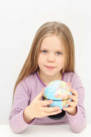 A cute girl with globe is dreaming about travels