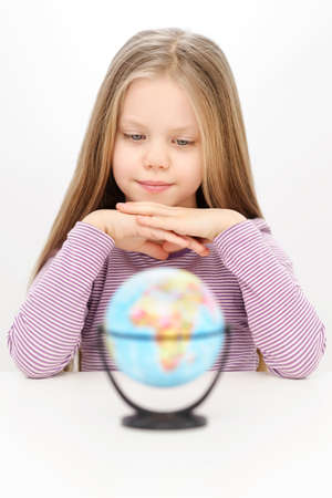 Beautiful confident young girl is watching at the world globe Stock Photo