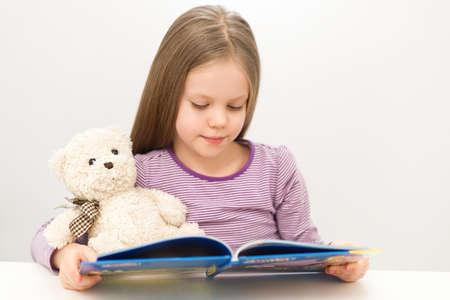 girl reading book: Cute little girl reading a book