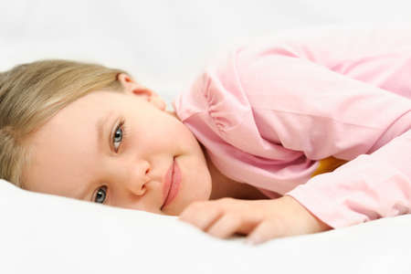 Young little girl is laying on bed with peaceful face expression Stock Photo