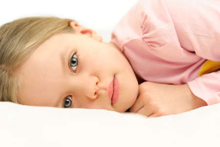 A little girl lying in bed with open eyes