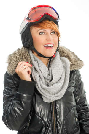 Winter woman in jacket, helmet and goggles watching at the sky Stock Photo
