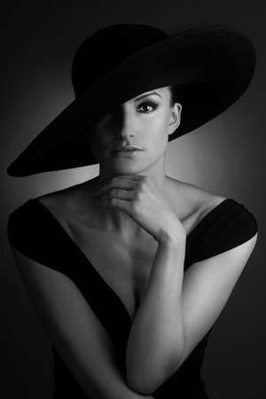 Young beautiful woman with retro big black hat
