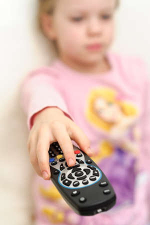 Portrait of cheerful young girl uses remote control to change television channels