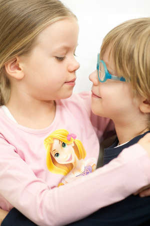 Little brother and sister holding and kissing each other photo