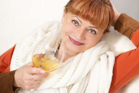 Mature woman with a glass of wine on sofa