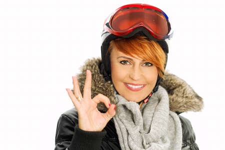 Winter woman in black jacket, helmet and goggles with fingers and sign OK
