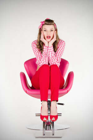 Surprised pin-up girl sitting on the chair