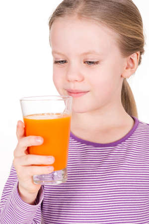 Young, smiling child looking and drinking orange juice