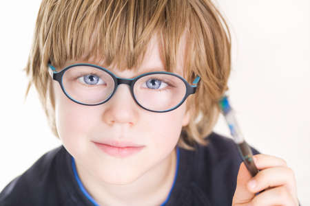 Beautiful boy with glasses and painting brush in hand