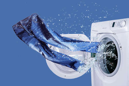 Washer and freshly laundered jeans Stockfoto