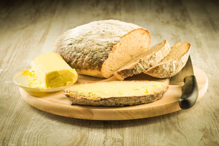 buttered: Bread on a wooden board and a slice of buttered bread Stock Photo