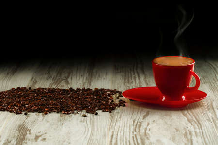 Coffee in the red cup on old boards with coffee beans