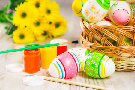 Easter concept, colorful Easter eggs with paints on a background of yellow flowers Reklamní fotografie