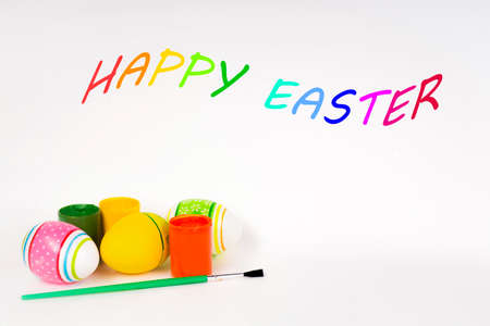 Easter concept, colorful Easter eggs with paints on a white background and the inscription