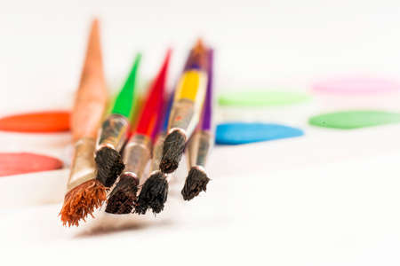 Concept of painting, colorful brushes and paints on a white background