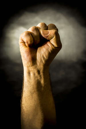A male hand in a gesture clenched in a fist on a lightened dark background