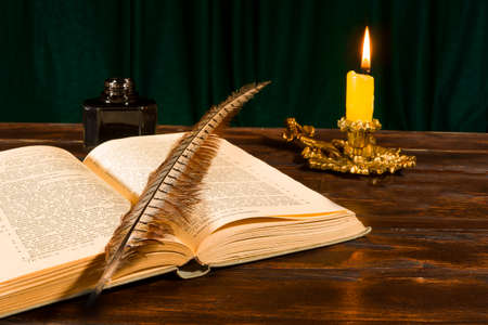 Education and writing concept, pen lying on a book, inkwell and a lit candle