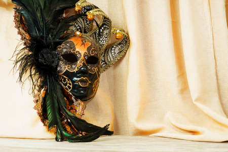 Venetian golden mask on a background of a light cloth