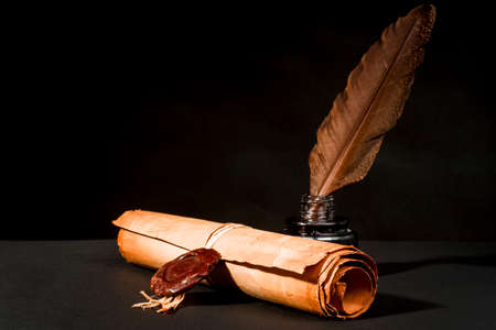 A papyrus scroll with a seal, a feather and an inkwell on a black background Foto de archivo