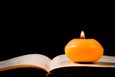 Lit candle standing on an open book, on a black background