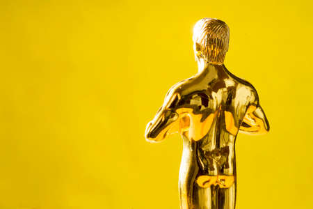 Golden statuette of a man on a yellow background Stock Photo